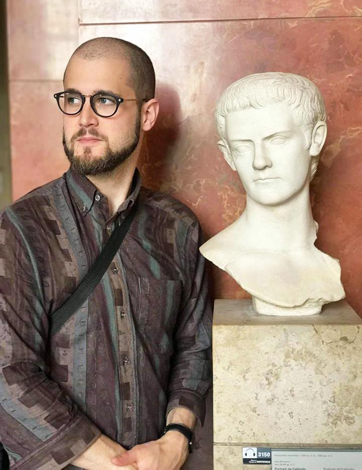 Режисер Жюль Одрі поруч із бюстом Калігули в Луврі